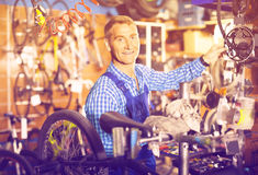 Male seller fixong bike in store. Friendly smiling man seller wearing uniform fixing bike wheel in store Stock Photography