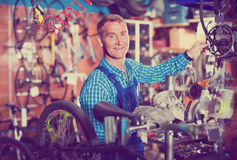Male seller fixong bike in store. Friendly smiling man seller wearing uniform fixing bike wheel in store Stock Image