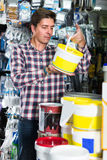 Male seller in hardware store is trading goods. For repair and painting Stock Photo