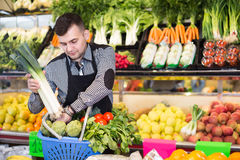 Male seller helping to choose. Male shopping assistant helping to buy fruit and vegetables in grocery shop Stock Image