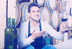 Male seller holding glass on wine in cellar. Friendly smiling male seller wearing apron holding glass on wine tasting in cellar Royalty Free Stock Photo