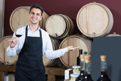 Male seller holding glass on wine in cellar. Happy smiling male seller in apron holding glass on wed wine in cellar with woods Stock Photography