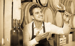 Male seller holding glass on wine in cellar. Joyful smiling male seller in apron holding glass on wine tasting in cellar Royalty Free Stock Photo