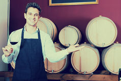 Male seller holding glass on wine in cellar. Joyful smiling male seller in apron holding glass on wine in cellar with woods Royalty Free Stock Image