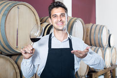 Male seller holding glass on wine in cellar. Positive male seller wearing apron holding glass on wine tasting in cellar Royalty Free Stock Images
