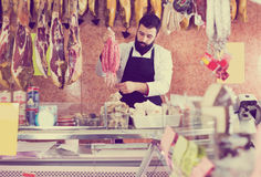 Male seller offering delicious sausages. Happy male seller offering delicious sausages in butcher's shop Stock Photos
