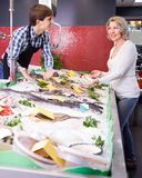 Male seller offering fish to mature customer in store. Young male seller offering fish to mature customer in store Stock Photo