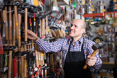 Male seller offering hammer. Experienced seller offering working tooling in household shop Royalty Free Stock Image