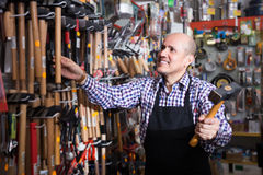 Male seller offering hammer. Experienced male seller offering working tooling in household store Royalty Free Stock Image