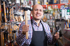 Male seller offering hammer. Mature male seller offering hammer in household shop Stock Photography