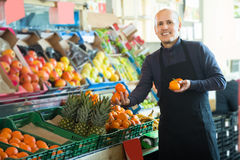Male seller offers mandarins Stock Image