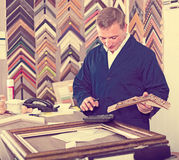 Male seller in picture framing studio with wooden details. Male seller standing in picture framing studio with wooden details Stock Photo
