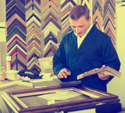 Male seller in picture framing studio with wooden details. Male seller standing in picture framing studio with wooden details Royalty Free Stock Images