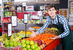 Male seller posing with apples, tangerines and bananas in store Stock Photo
