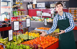 Male seller posing with apples, tangerines and bananas in store. Happy american male seller posing with apples, tangerines and bananas in store Stock Images