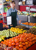 Male seller posing with apples, tangerines and bananas in store Stock Photography