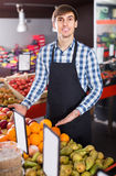 Male seller posing with apples, tangerines and bananas in store Royalty Free Stock Photo