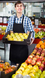 Male seller posing with apples, tangerines and bananas in store Royalty Free Stock Photography