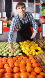 Male seller posing with apples, tangerines and bananas in store Royalty Free Stock Images