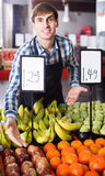 Male seller posing with apples, tangerines and bananas in store Stock Photos