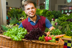 Male seller posing with basket of vegetables. Royalty Free Stock Images