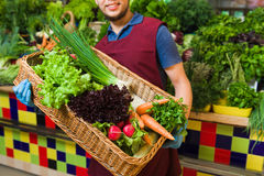 Male seller posing with basket of vegetables. Stock Images