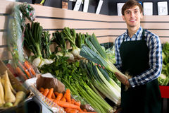 Male seller posing with celery. Cheerful male seller posing with celery, parsley and leek in store Stock Image