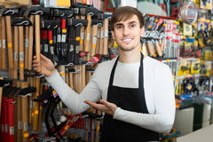 Male seller posing at tooling section of household store. Adult male seller posing at tooling section of household store Stock Images