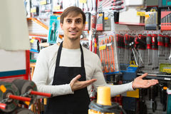 Male seller posing at tooling section of household store. Positive male seller posing at tooling section of household store Royalty Free Stock Image