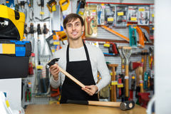Male seller posing at tooling section. Ordinary male seller posing at tooling section of household shop Royalty Free Stock Images