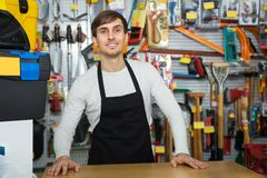 Male seller posing at tooling section. Ordinary young male seller posing at tooling section of household store Royalty Free Stock Images