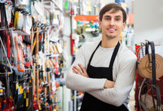 Male seller posing at tooling section. Young male seller posing at tooling section of household shop Royalty Free Stock Photo