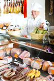 Male seller posing with wursts in butchery. Glad mature male seller posing with wursts in butchery Stock Photo