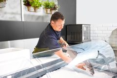 Male seller putting trout to fridge at fish shop. Food sale, small business and people concept - male seller putting trout to fridge at fish shop Royalty Free Stock Images