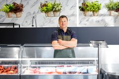 Male seller with seafood at fish shop fridge. Food sale, small business and people concept - male seller with seafood at fish shop fridge Stock Photos