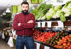 Male seller standing  near the shelves  in grocery shop. Smiling male seller standing  near the shelves  in grocery shop Royalty Free Stock Photos