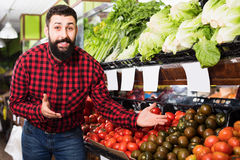 Male seller standing  near the shelves with tomatoes. Smiling male seller standing  near the shelves with tomatoes in grocery shop Royalty Free Stock Photos