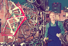 Male seller in uniform picking new bicycle wheel hands Royalty Free Stock Photos