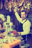 Male seller weighing piece of meat in butcher's shop. Adult european male seller weighing piece of meat in butcher's shop Royalty Free Stock Photography