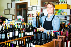 Male seller with wine bottle in hands Royalty Free Stock Photography