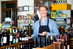 Male seller with wine bottle in hands. Portrait of positive male seller wearing uniform with wine bottle in hands in wine shop Stock Image