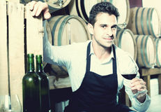 Male seller in wine store. Glad man seller in apron holding glass of red wine in shop with wooden barrels Stock Photo