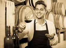 Male seller in wine store. Glad man seller in apron holding glass of red wine in shop with woods Stock Photo