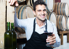 Male seller in wine store. Portrait of cheerful man seller in apron holding glass of red wine in shop with woods Stock Photo