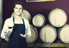 Male seller in wine store. Portrait of happy man seller in apron holding glass of red wine in shop with woods Stock Image