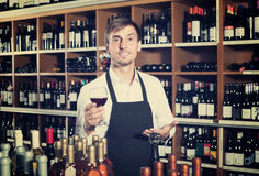 Male seller in wine store. Portrait of male seller in uniform promoting to taste wine before purchasing it in wine store royalty free stock images