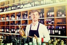 Male seller in wine store. Smiling friendly male seller in uniform posing with bottle wine in hands in wine store Stock Photo