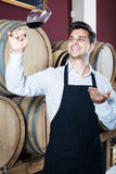 Male seller in wine store. Smiling man seller in apron holding glass of red wine in shop with woods Royalty Free Stock Photos