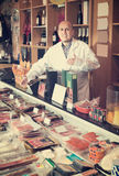 Male seller with wurst and jamon. In meat store Stock Photo