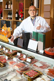Male seller with wurst and jamon. In meat store counter Stock Image